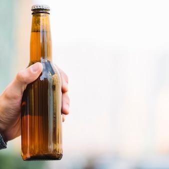 Mano sosteniendo la botella de cerveza