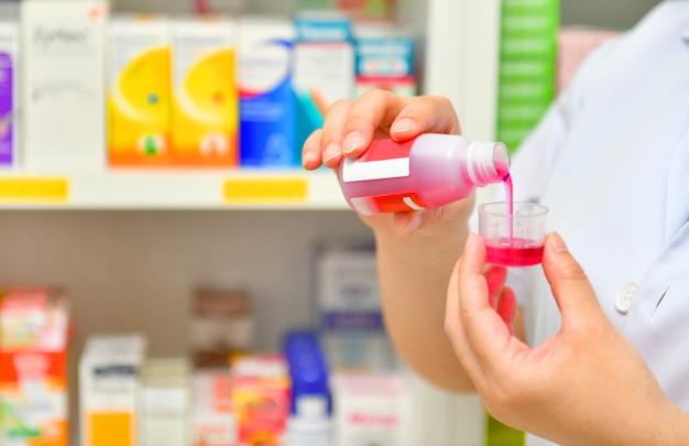 Mano sosteniendo una botella de jarabe para la tos en farmacia farmacia