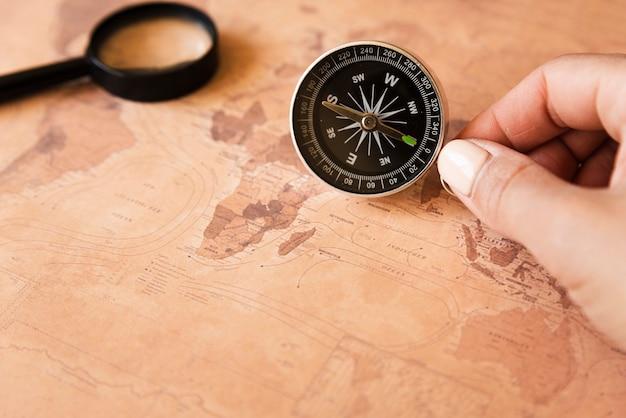 Mano sosteniendo una brújula en un mapa
