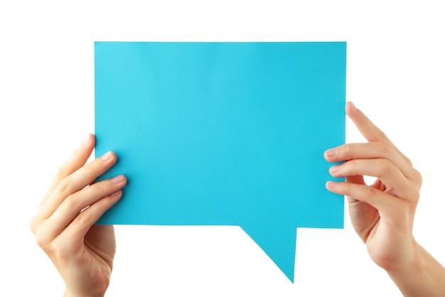 Mano sosteniendo una burbuja de discurso vacío azul aislado sobre fondo blanco.
