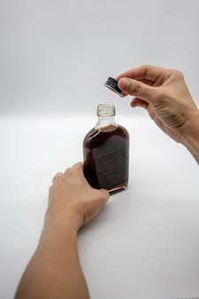 Mano sosteniendo el café cold brew en botella de vidrio con tapa negra aislada en blanco