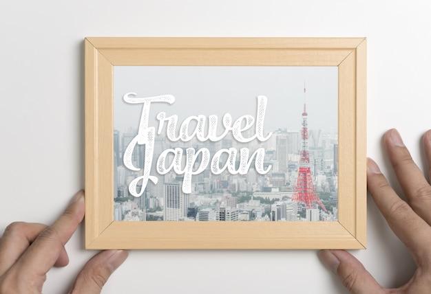 Mano sosteniendo el cartel de viaje japón tokio en marco de fotos