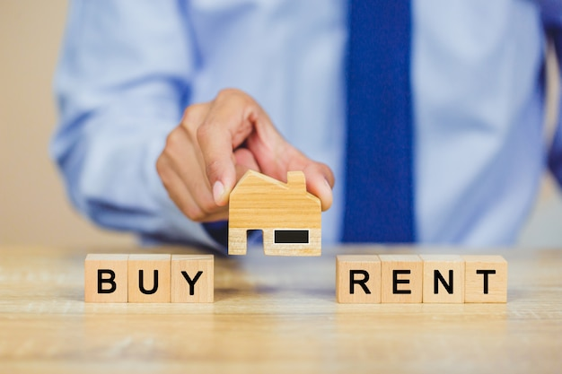 Mano sosteniendo casa con compra o alquiler, concepto inmobiliario.