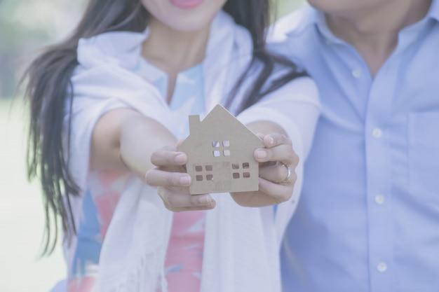 Mano sosteniendo una casa de madera