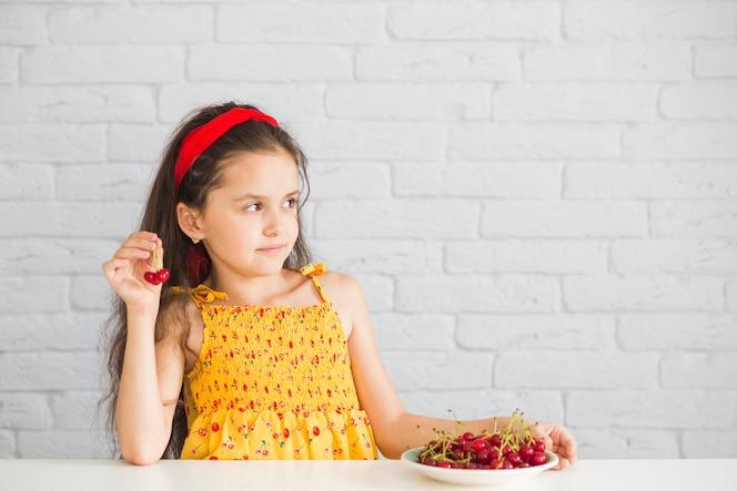 Mano sosteniendo cerezas rojas en frente de la pared de ladrillo