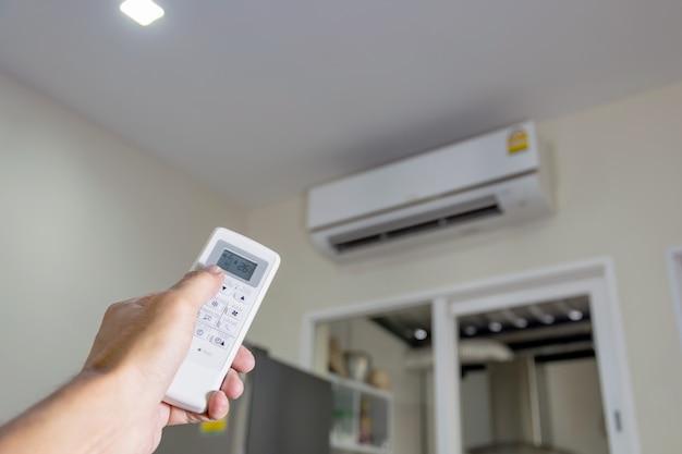 Mano sosteniendo el control remoto para controlar el aire acondicionado en la habitación.