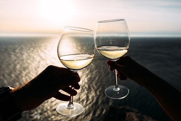 Mano sosteniendo una copa de vino sobre el mar. chin-chin. vacaciones románticas. dos manos sosteniendo copas de vino contra el mar. copia espacio