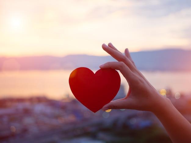 Mano sosteniendo corazón rojo durante el atardecer de fondo.