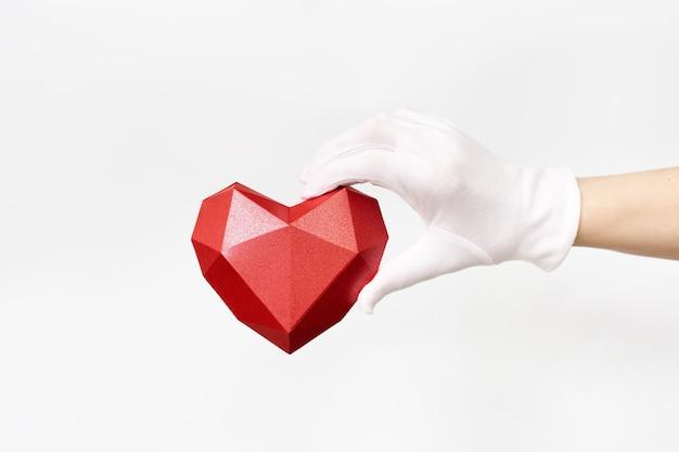 Mano sosteniendo corazón rojo sobre blanco