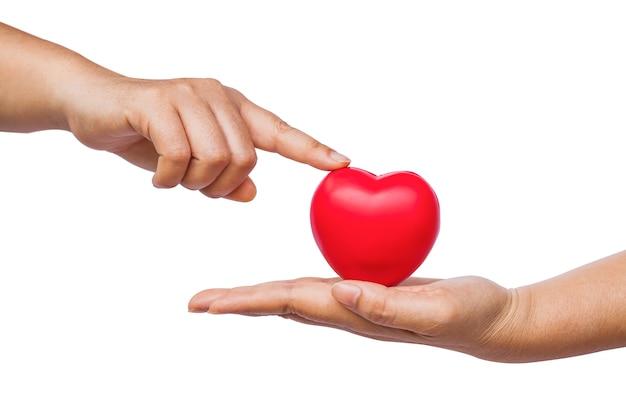 Mano sosteniendo un corazón rojo sobre fondo blanco