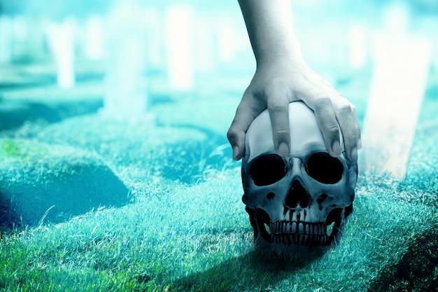 Mano sosteniendo un cráneo humano en el cementerio con el fondo de la escena nocturna