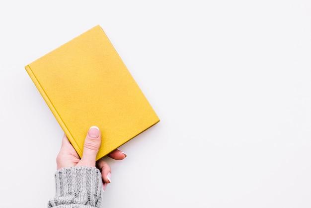 Mano sosteniendo cuaderno cerrado