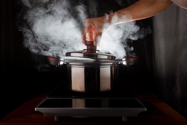 Mano sosteniendo la cubierta de olla de metal con vapor caliente que fluye desde el interior