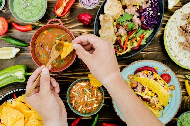 Mano sosteniendo cuchara y nacho cerca de comida mexicana