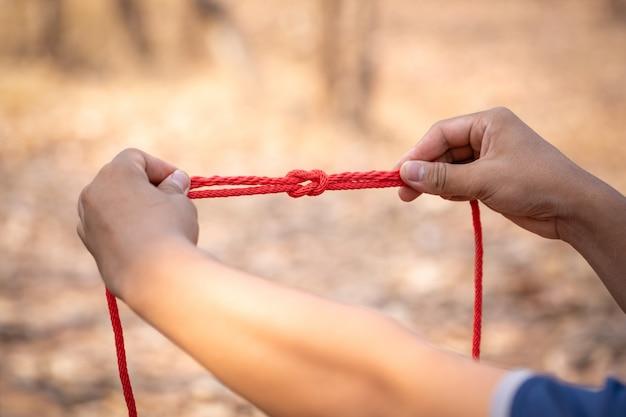 Mano sosteniendo la cuerda para aprender nudo scout