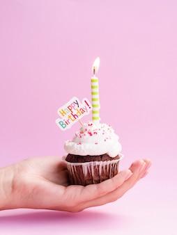Mano sosteniendo delicioso muffin con cartel de feliz cumpleaños