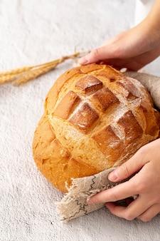 Mano sosteniendo delicioso pan horneado y tela de arpillera