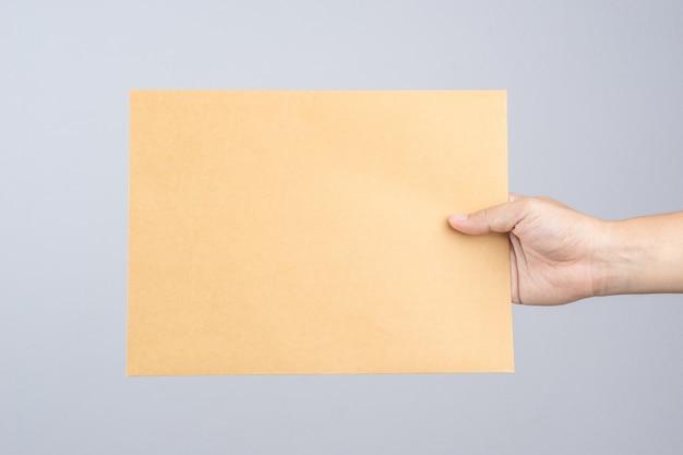 Mano sosteniendo un documento autoadhesivo sobre marrón