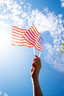 Mano sosteniendo dos banderas americanas en el cielo azul con fondo de luz solar, ondeando la bandera de estados unidos de cerca