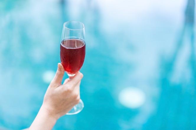 Mano sosteniendo el vaso de vino tinto en la piscina