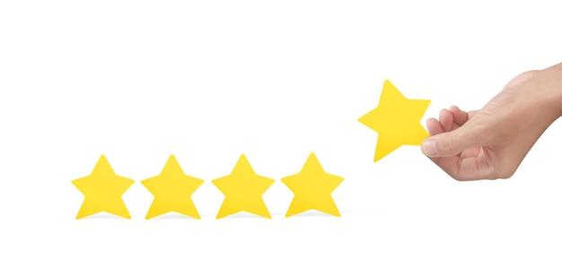 Mano sosteniendo una estrella amarilla. aumentar el concepto de evaluación y clasificación de calificaciones