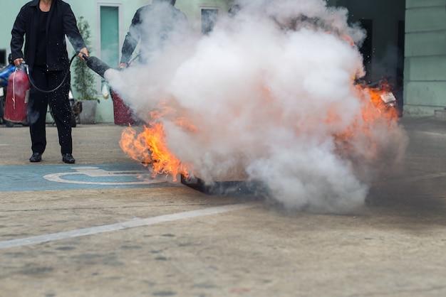 Mano sosteniendo el extintor de incendios y rociando al fuego ardiente