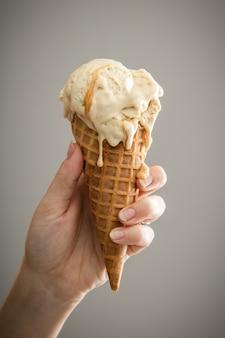 Una mano sosteniendo un helado de caramelo derretido