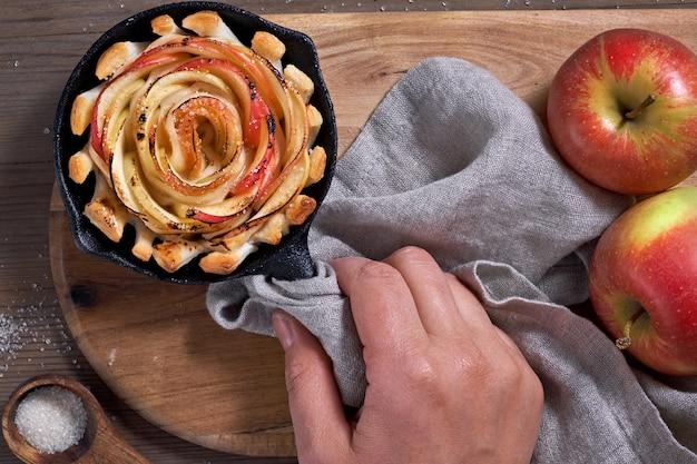Mano sosteniendo hojaldre omemade con rodajas de manzana en forma de rosa al horno en sartén de hierro