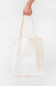 Mano sosteniendo la bolsa de lona de tela blanca en blanco aislada sobre fondo blanco