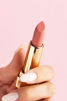 Mano sosteniendo lápiz labial rosa