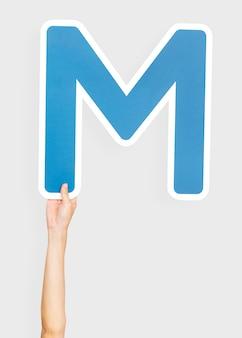 Mano sosteniendo la letra m