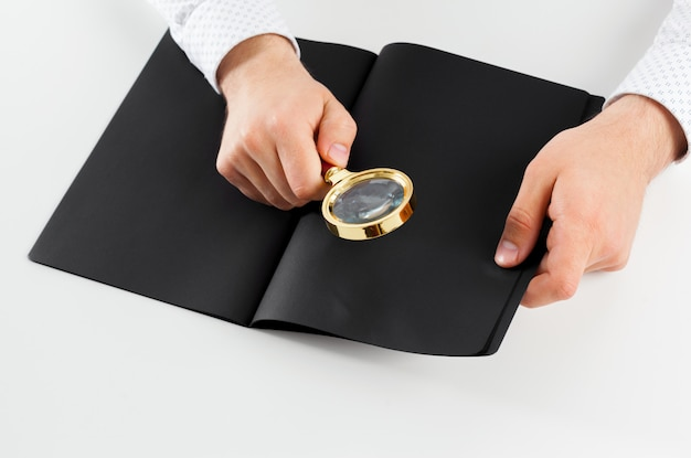 Mano sosteniendo el libro abierto en blanco simulacro