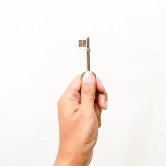 Mano sosteniendo la llave aislada en blanco