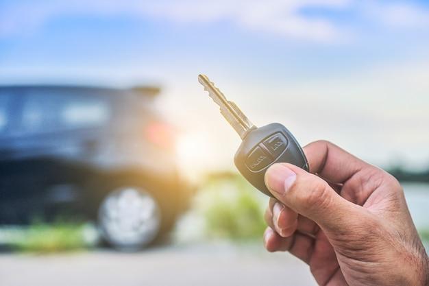 Mano sosteniendo la llave y el automóvil estacionado en la carretera