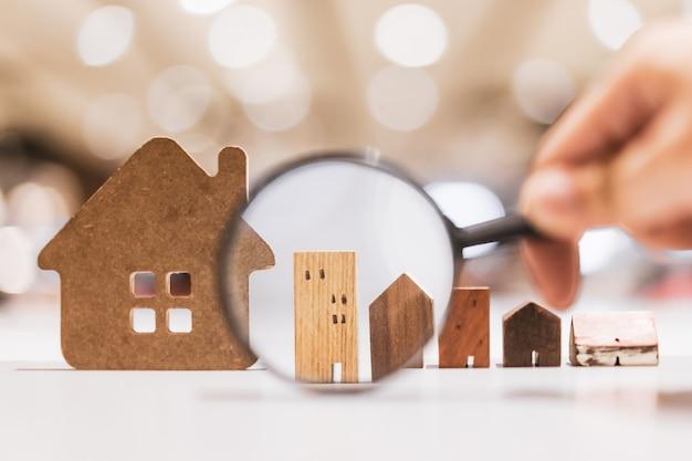 Mano sosteniendo la lupa y mirando el modelo de la casa