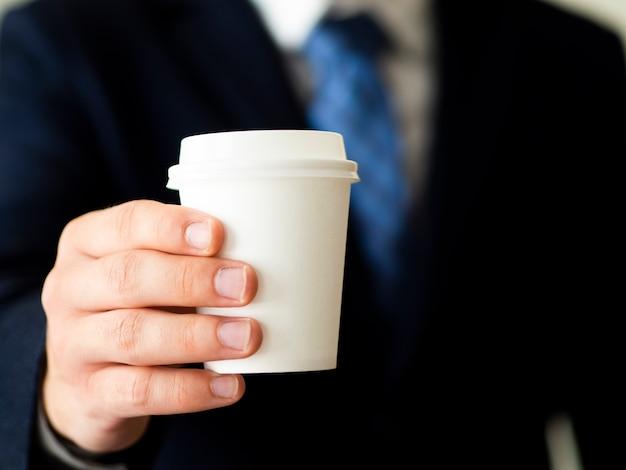 Mano sosteniendo maqueta de taza de café