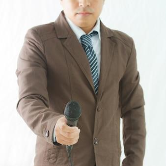 Mano sosteniendo un micrófono realizando una entrevista de negocios