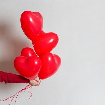 Mano sosteniendo un montón de globos