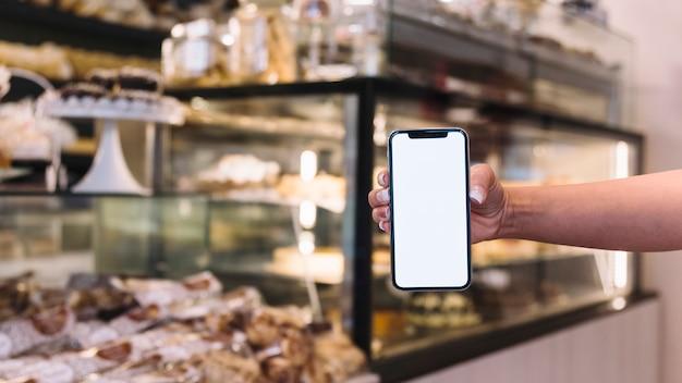 Mano sosteniendo móvil delante de mostrador