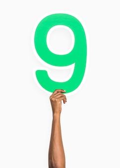 Mano sosteniendo el número 9