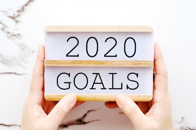 Mano sosteniendo objetivos 2020 en caja de madera sobre pared de mármol
