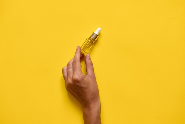 Mano sosteniendo ottle con suero o aceite de esencia natural.