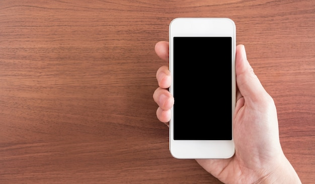 Mano sosteniendo la pantalla vacía del teléfono móvil sobre la mesa
