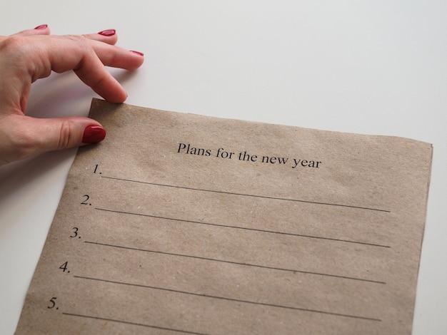 Mano sosteniendo papel con planes para el nuevo año