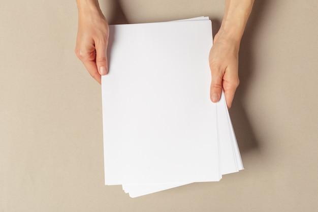 Mano sosteniendo papeles tamaño a4