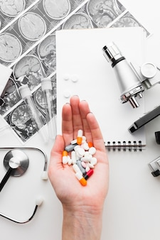 Mano sosteniendo pastillas médicas planas