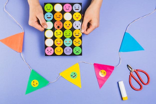 Mano sosteniendo pegatinas de emoji cerca de un empavesado colorido con tijera y pegamento en barra