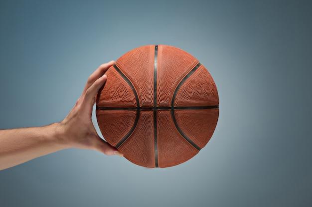 Mano sosteniendo una pelota de baloncesto