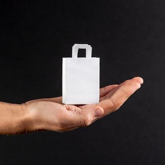 Mano sosteniendo una pequeña bolsa de papel