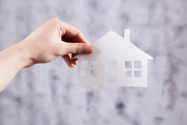Mano sosteniendo una pequeña casa en un gris